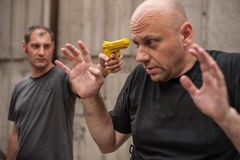 Self defense techniques against a gun. Kapap instructor demonstrates self defense techniques against a gun royalty free stock images
