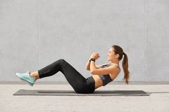 Self determined sporty woman with pony tail, dressed in leggings, top, sneakers, smartwatch makes on press, wants to have muscular. Body, has workout in in gym stock photography