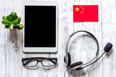Self-development. Learning chinese online. Headphones and tablet PC on wooden background top view mockup Stock Photography