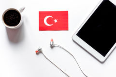 Self-education. Learning turkish online. Headphones and tablet PC on white table background top view mockup. Self-education. Learning languages online Royalty Free Stock Photos