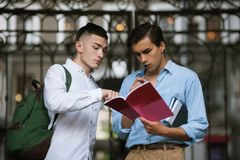 Self-education for students. Homework outdoors. Two attentive stylish young males, break in University Stock Photo
