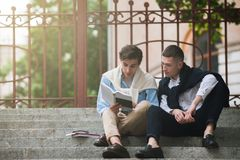 Self-education for young men. Modern street style. Self-education for two young men. Modern street style. Break in University outdoors, reading concept Royalty Free Stock Image