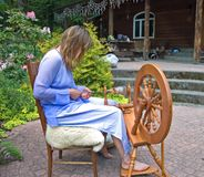Self Employed Business Woman Working. This artisan woman is hand crafting wool into homespun yard using a spinning wheel at her home in which she is self Stock Photography