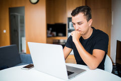 Self employed businessman thinking and look working from home on laptop Royalty Free Stock Photo