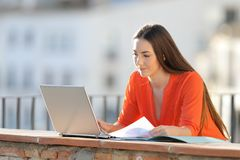 Self employed checking laptop holding documents. In a balcony royalty free stock photo