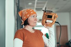 Self employed female carpenter with electric jigsaw stock photos