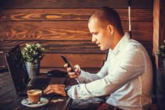 Self employed happy man working with a laptop and a smart phone. In cafe Stock Photo