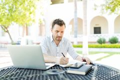 Self-Employed Man Preparing Schedule In Garden. Self-employed man with laptop and books preparing schedule at table in garden royalty free stock image