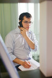 Self-employed man working at home. Talking on phone Royalty Free Stock Image