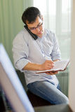 Self-employed man working at home. Talking on phone Stock Photography