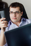 Self-employed man working at home. Talking on phone Royalty Free Stock Images