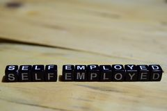 Self employed message written on wooden blocks. Education and motivation concepts. Cross processed image on Wooden Background stock photo