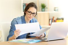 Self employed working comparing documents at home. Serious self employed working comparing documents on a table at home Royalty Free Stock Photo