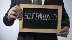 Self-employed written on blackboard, businessman holding sign, business concept stock video