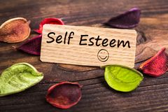Self esteem text in card. Self esteem text in wooden card with dried flower on wood royalty free stock images