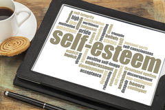 Self-esteem word cloud. On a digital tablet with cup of coffee royalty free stock images