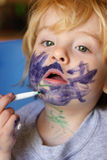 Self expression. Toddler boy exploring art by drawing on his face with a marker