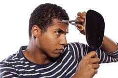 Self haircut. Dark-skinned boy haircut himself with scissors royalty free stock photography