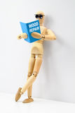Self-Help. Wooden artist manikin reading a book on wood repair while leaning on a wall Stock Photography