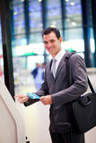 Self help check in. Businessman using self help check in machine at airport Stock Photography