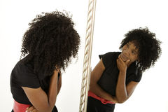 Self image. Lady looking at herself in mirror with quizzical expression Stock Image