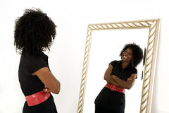 Self image. Lady looking at herself in mirror with a smile Royalty Free Stock Photography