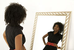 Self image. Lady looking at herself in mirror with a smile Stock Photography