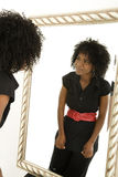 Self image. Lady looking at herself in mirror with a smile Stock Photo