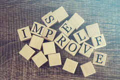 Self Improve message formed with wooden blocks Stock Photos