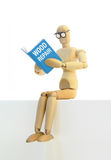 Self-Improvement. Wooden manikin sitting down reading a book on wood repair Stock Photos