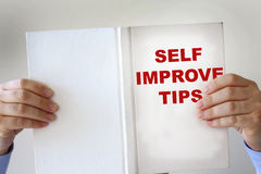 Self improvement fake book. Hands holding a self improvement how to book Stock Image
