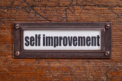 Self improvement label. Self improvement  - file cabinet label, bronze holder against grunge and scratched wood Royalty Free Stock Images