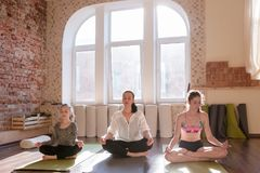 Self-improvement together. Women meditation class. Thoughts concentration, Young meditating girls in yoga studio with instructor. Teenage sport, gym background Royalty Free Stock Images