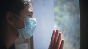Self-isolation. little girl looks out the window sad in a medical gauze mask.coronavirus concept pandemic virus covid