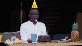 Self isolation. Sad lonely African young handsome man blows whistle alone celebrating his own birthday with cake at home