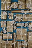 Advent calendar with 24 presents on teal. Self made advent calendar with twenty four presents wrapped in golden paper on teal wood Royalty Free Stock Images