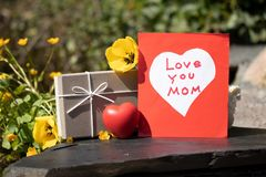 "Self made card, white heart on red background, a gift box and a. Red heart. On card is written ""Love You Mom"". Card, gift box and red heart are presented on Stock Image"