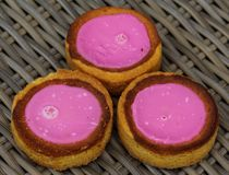 Self made Dutch Butter Cake Boterkoek cookie with pink glaze, fresh baked from the oven. Displayed on wooden background. Close up of Self made Dutch Butter Cake royalty free stock images