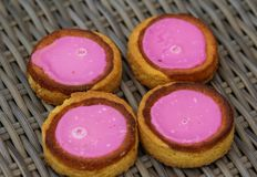 Self made Dutch Butter Cake Boterkoek cookie with pink glaze, fresh baked from the oven. Displayed on wooden background. Close up of Self made Dutch Butter Cake royalty free stock photos