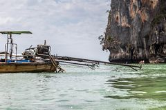 The self-made engine from the pickup truck is mounted on a long-tailed motor boat against the background of a sandy beach with. Tourists. Thailand krabi royalty free stock images