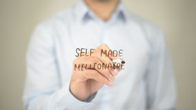 Self Made Millionare, Man Writing on Transparent Screen. High quality Stock Photo