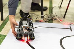 Self-made robot from Lego blocks. Human hand. Stock Photo