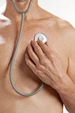 Man Checkup Stethoscope Heart. A man using a stethoscope to check his own heart Stock Images