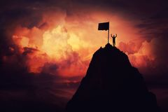 Climb to finish flag. Self overcome concept as a businessman lift his hands up on the top of al mountain reaching the finish flag. Road to win and success over royalty free stock images