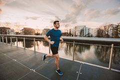 Self overcome conquering obstacles and win. Young athletic man practicing sport outdoors, running fast along bridge over the sunset sky background. Self overcome stock photos