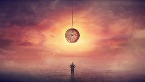 Self overcome, time travel concept, achieving success. Surreal scene as confident businesswoman stands on the in front of a huge clock hanging from the sunset royalty free stock images
