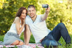 Self portrait. Beautiful young couple taking a self portrait  in the park Stock Image