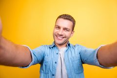Self portrait of attractive, cute, smiling man with bristle, stu. Bble in jeans shirt, shooting selfie with two hands on front camera over yellow background royalty free stock photo
