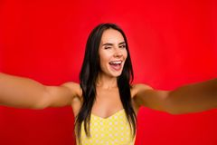 Self portrait of funky, cheerful, pretty, charming, sweet, cute, nice girl shooting selfie on front camera of smart phone winking. With one eye, isolated on red royalty free stock photos