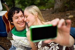 Self Portrait Outdoor Couple. A happy playful couple on a picnic taking a self portrait royalty free stock photo